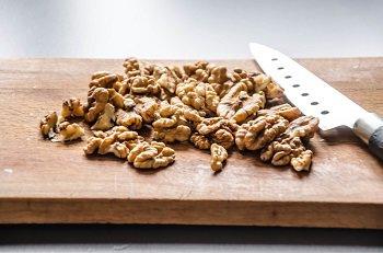 Крупно рубим ножом грецкие орехи и чеснок