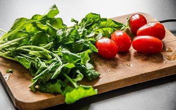 Помытые руккола и помидоры черри для салата с креветками