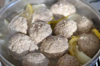 Тефтели варятся в бульоне с  луком и лимоном