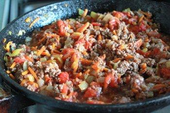 К фаршу и овощам добавляется вино и измельченные помидоры