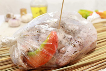 Тушку упаковывают в кулинарный рукав который завязывают с обеих сторон