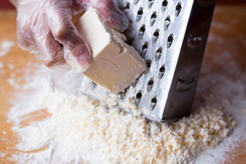 Замерзшее сливочное масло натирается на терке в муку