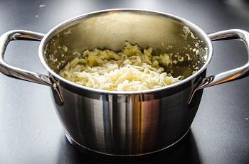 В горячий картофель добавляем натертый сыр и тщательно размешиваем