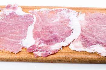 Кусочки отбитого мяса на разделочной доске