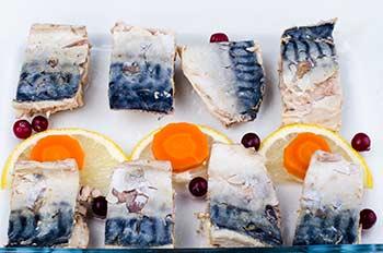 Выложить рыбу в емкость украсить клюквой налить бульон и на холод