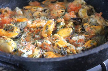 Обжариваются мидии с чесноком помидором и базиликом