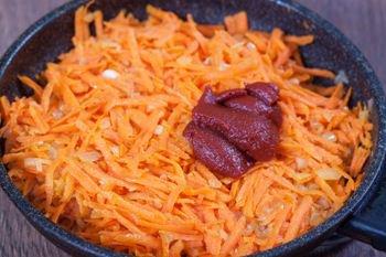 В томленную с луком морковь выкладываем томатную пасту