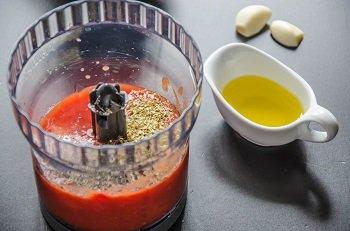 В блендере пробиваются помидоры с чесноком и оливковым маслом