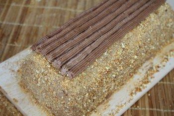 Торт посыпанный крошкой и украшенный полосками шоколадного крема