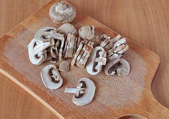 Помытые шампиньоны порезанные тонкими ломтиками