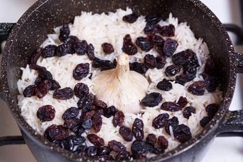 Мясо с овощами прикрыть рисом изюмом воткнуть головку чеснока