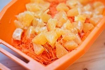 Чистим цитрус разделяем на дольки режем на кусочки отправляем к моркови