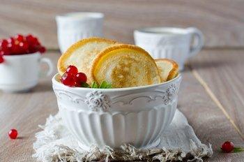 Подавать оладьи с сахарной пудрой ягодами медом сметаной