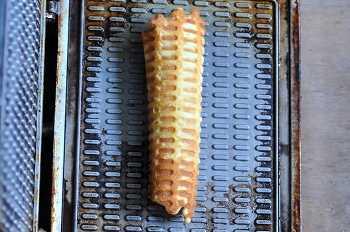 Деревянной лопаткой готовую вафлю приподнять с вафельницы и свернуть