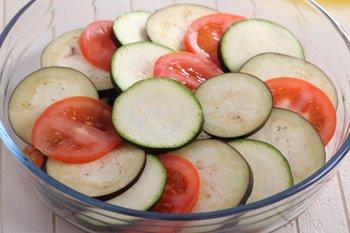 Поверх соуса выложен слой кружков из помидоров баклажан и кабачков