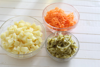 Нарезанные кусочками картофель натертые соленые огурцы и морковь для супа