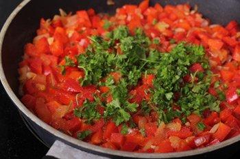 Мелкопорезанная петрушка соль и перец добавляются в тушеную смесь помидоров и болгарского перца