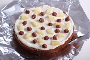 Основа торта покрытая кремом с кусочками ананасов и орехами