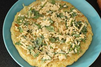 На блинчик из теста с кабачками нанесен крем из сыра с чесноком и зеленью