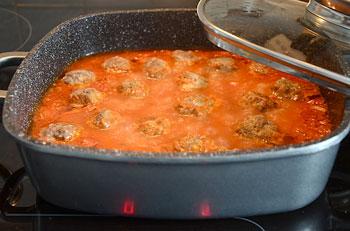 Опускаем в соус мясные шарики уменьшаем огонь и тушим под крышкой