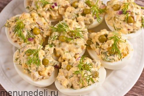 Готовые яйца, фаршированные кальмарами на белой тарелке