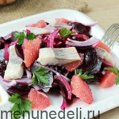 Свекольный салат с селедкой и грейпфрутом подача на белой тарелке