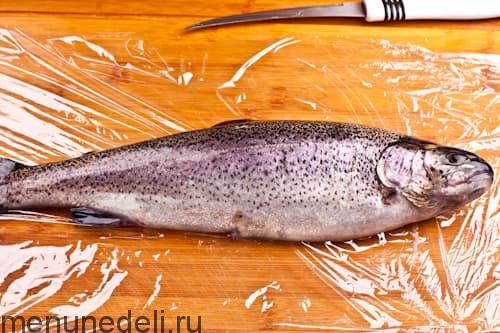 Подготовленная рыба - радужная форель, фаршированная лимоном и петрушкой