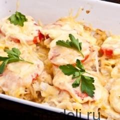 Присыпать готовую рыбу с луком и помидором под сыром зеленью