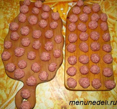 Приготовленные фрикадельки на разделочных досках перед замораживанием