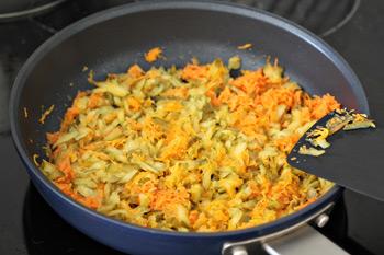Натертые морковь и огурцы жарятся на сковородке для супа